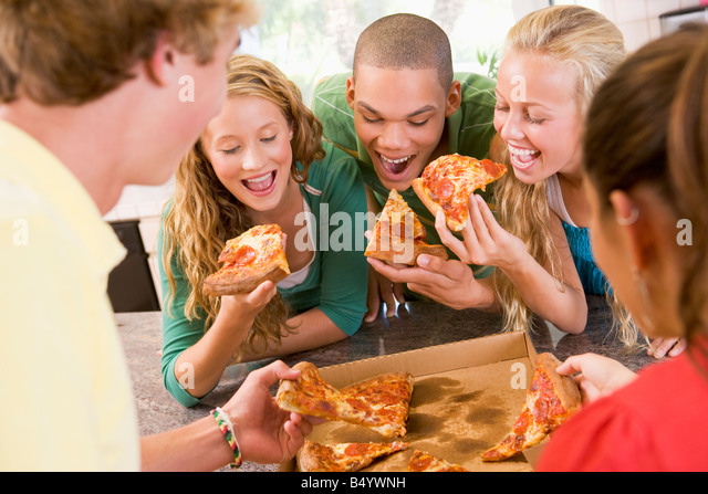 Group Of Teenagers Eating Pizza - Stock Image