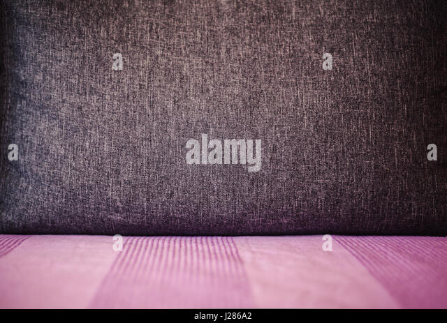 Abstract composition of big gray pillow on purple bed. - Stock Image