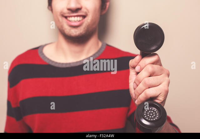 A happy young man is holding a telephone receiver - Stock Image