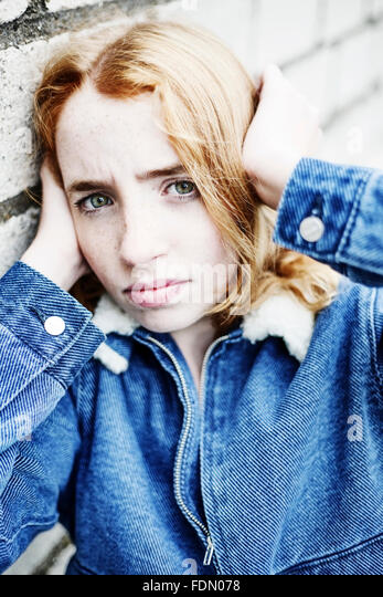 Timid girl, red-haired, putting her hands over her ears, portrait, Germany - Stock Image