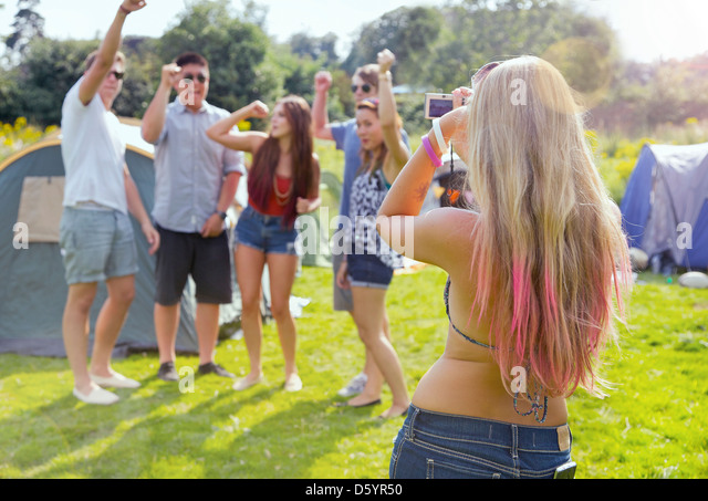 Back View of Woman Taking a Photograph of Group of Teenagers - Stock Image