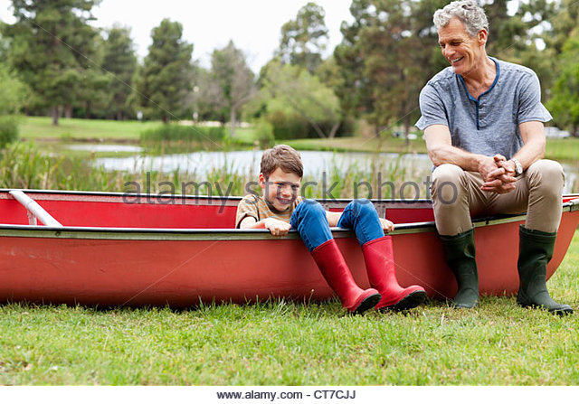 Grandfather and grandson sitting on canoe - Stock Image