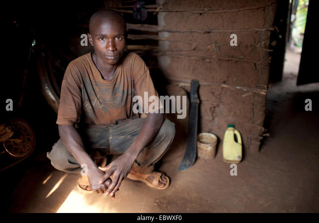 young man squatting in the entrance of his humble mud house with a machete beside him, Burundi, Karuzi, Buhiga - Stock Image