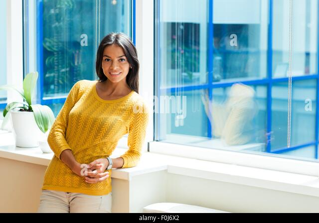 Smiling attractive businesswoman standing near window in office and looking at camera - Stock Image