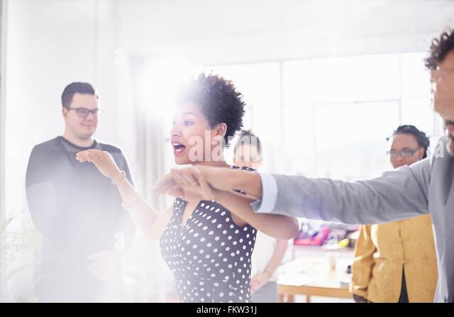 Colleagues in team building task, holding hands covering eyes - Stock Image
