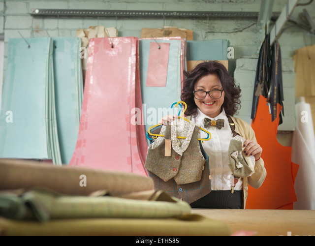 Fashion designer with childrens wear in clothing factory, portrait - Stock Image