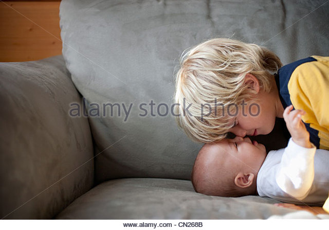 Boy face to face with baby brother on sofa - Stock-Bilder