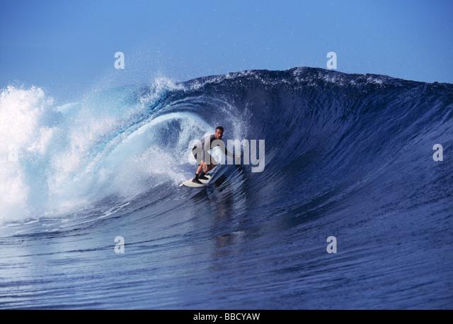 A surfer catches a perfect wave at Cloudbreak near the Fuji Island of Tavarua - Stock Image