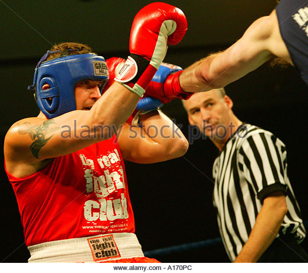 Referee watching boxers at The Real Fight Club, White Collar Boxing, Grosvernor Square, London, England. - Stock Image