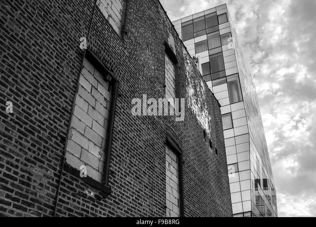 A contrast of an old brick building with a modern glass tower in monochrome. Shot in NYC. - Stock Image