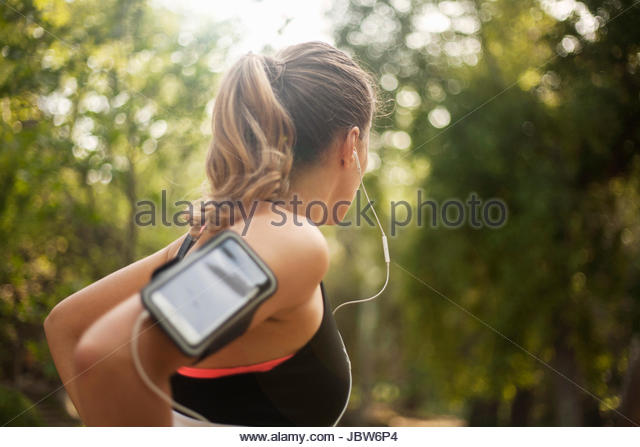 Young woman outdoors, wearing sports clothing and earphones, smartphone attached to arm - Stock-Bilder