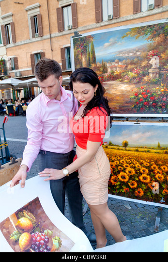 Couple flipping through art posters in Piazza Navona Rome Italy - Stock-Bilder