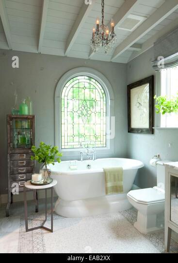 Contemporary bathroom with large window and ceramic tub. - Stock-Bilder
