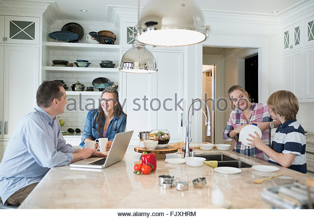 Brother and sister doing dishes while parents talk - Stock Image