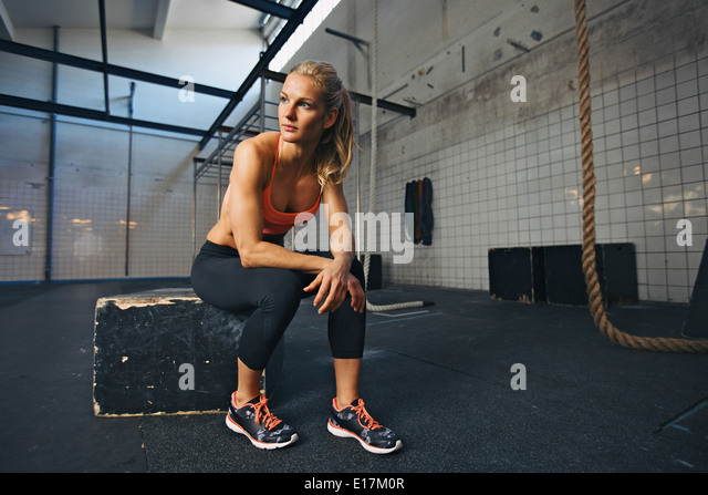 Young woman sitting on a box at gym after her workout. Caucasian female athlete taking rest after exercising at - Stock Image
