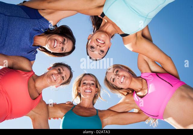 Smiling women standing in circle - Stock Image