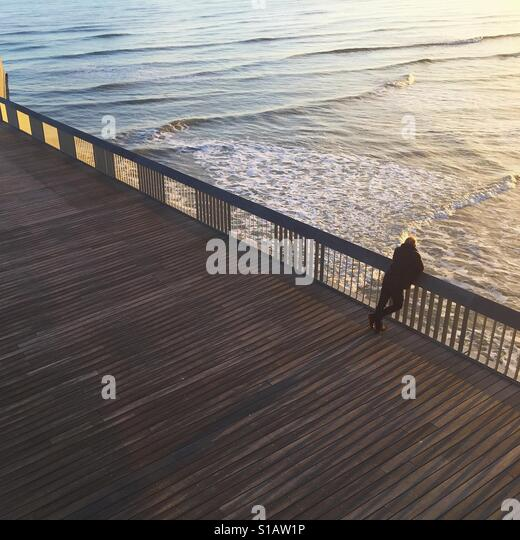Man leaning over Hastings pier looking at the sea - Stock-Bilder
