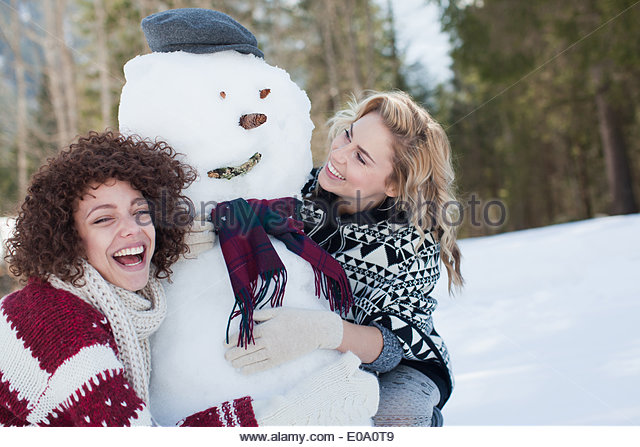 Two women hugging snowman - Stock Image