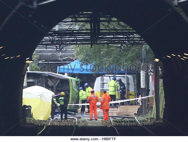 Members of the emergency services work at the scene of an accident where a tram overturned killing 7 people and - Stock-Bilder
