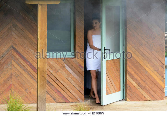 Young woman at door to outdoor bathroom. - Stock Image