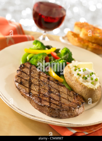 Steak dinner served with a loaded baked potato, vegetables, garlic bread and a glass of wine - Stock Image