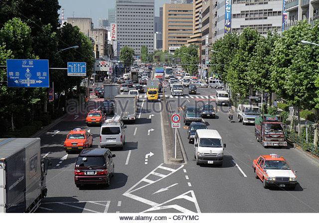 Japan Tokyo Tsukiji Shin-ohashi Dori street scene traffic taxi cabs signs buildings kanji hiragana characters Japanese - Stock Image