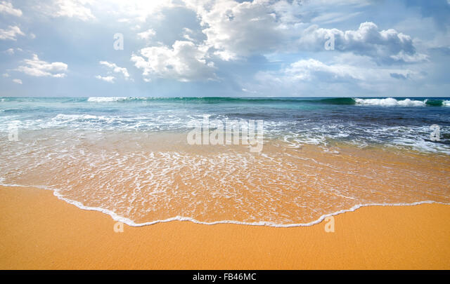 Waves of the ocean on a sandy coast - Stock Image