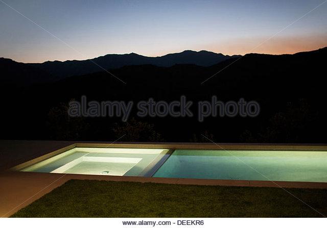 Exterior of modern house and swimming pool at night - Stock Image