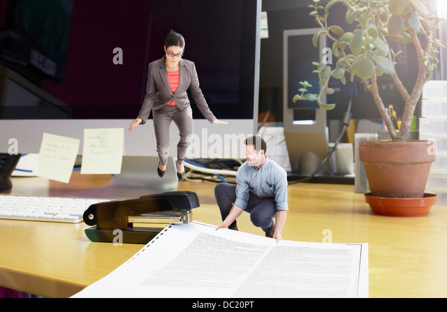 Mid adult business colleagues stapling large document on oversized desk - Stock Image
