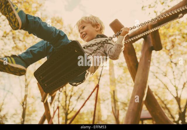 Toddler having fun on a swing - Stock Image