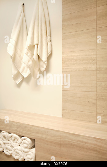 White towels hanging and rolled up in modern spa - Stock Image