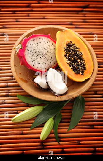 Dragon fruit, Papaya and Coconut in wooden bowl on bamboo background - Stock Image