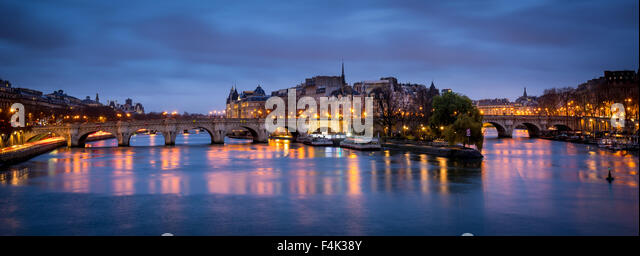 Ile de la Cite and Pont Neuf at dawn. The calm Seine River reflects the cloudy morning sky and street lamp lights. - Stock Image