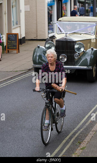 Older woman carrying a croquet mallet cycles in front of a vintage Rolls Royce wedding car - Stock Image