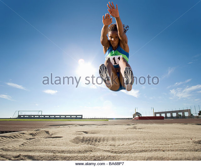 African female athlete mid-air during long jump - Stock Image