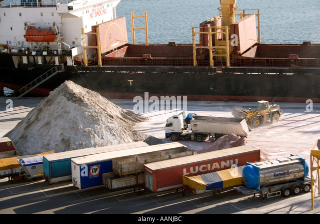 Shipment of salt at Cagliari Dockside, Sardinia, Cagliari Port Sardinia truck lorry ship shipping hold container - Stock Image