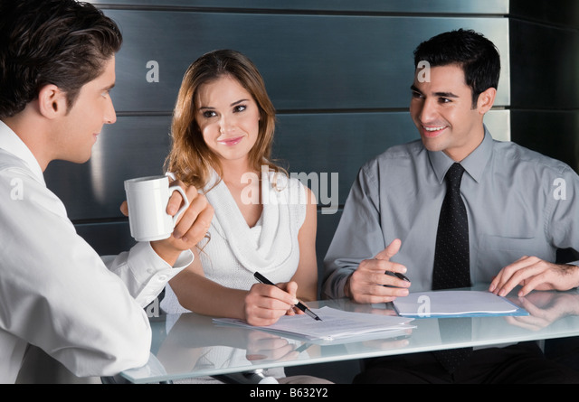 Two businessmen and a businesswoman talking in an office - Stock Image