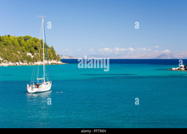 Lakka, Paxos, Ionian Islands, Greece. View across the clear turquoise waters of Lakka Bay, yacht anchored offshore. - Stock Image