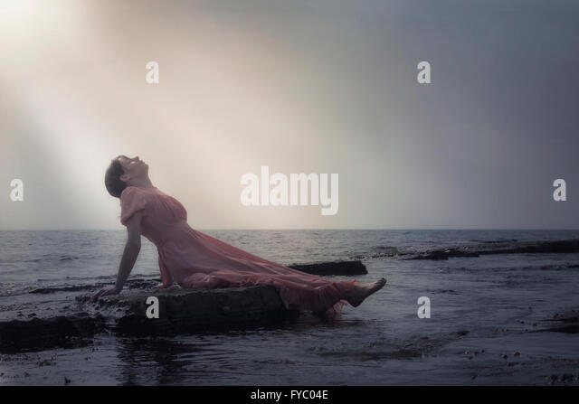 a woman in a pink dress is lying on stones at the sea - Stock Image