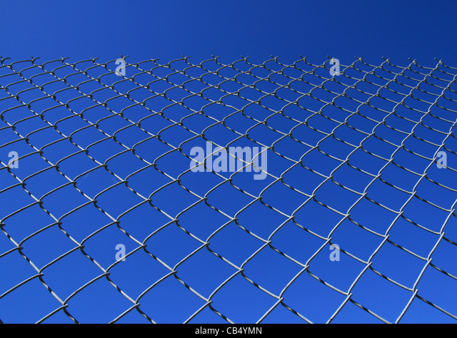 chain link fence against a blue sky - Stock Image