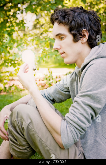 Young man holding glowing lightbulb - Stock Image