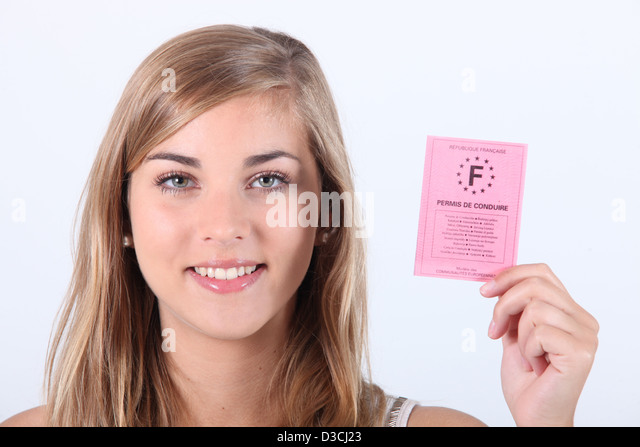 Blonde girl showing driving license - Stock Image
