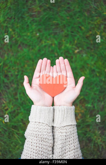 Woman holding a paper heart in her hands - Stock-Bilder