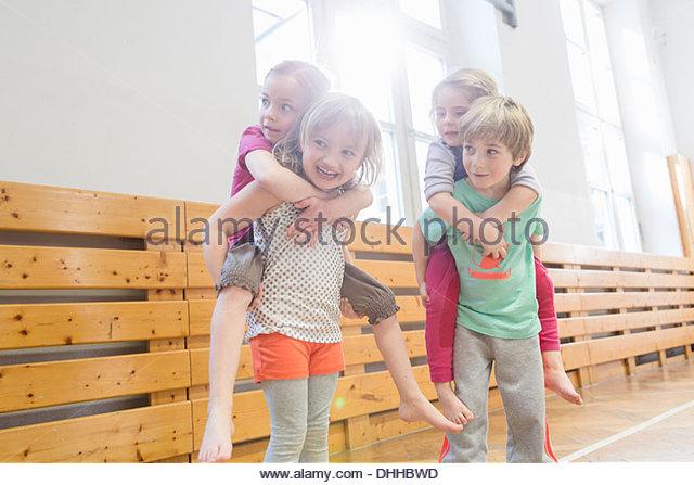 Children giving friends a piggy back - Stock Image