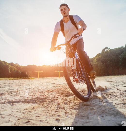 Biker riding along beach at sunset - Stock Image