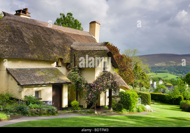 Pretty thatched cottage in the picturesque village of Selworthy, Exmoor National Park, Somerset, England. Spring - Stock-Bilder