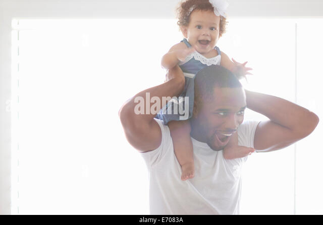 Father holding baby daughter on his shoulders - Stock Image