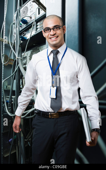 Portrait of a technician smiling in a server room - Stock Image