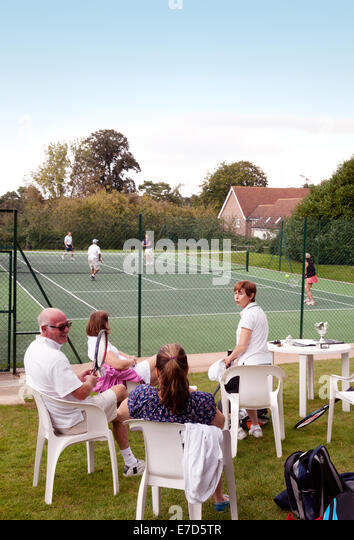 People enjoying an afternoon playing tennis at the URC Tennis Club, a local tennis club, Newmarket, Suffolk, England - Stock Image