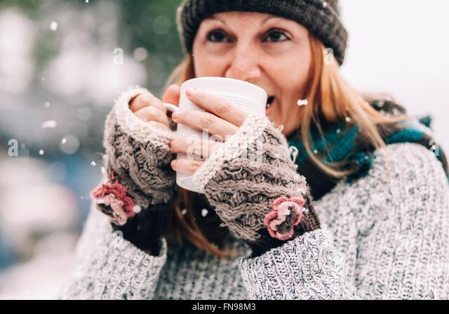 Woman standing in snow holding hot drink - Stock-Bilder
